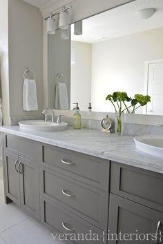 basement bathroom.  Simple.   gray double bathroom vanity, shaker cabinets, frameless mirror, white oval vessel sinks, marble countertop. don't like sconces.