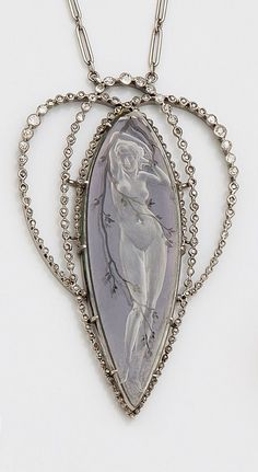 RENÉ LALIQUE - An Art Nouveau platinum, diamond and rock crystal pendant, about 1900. The articulated necklace with oval interlacing links set with old and rose-cut diamonds, set to the centre with a rock crystal navette-shaped plaque engraved with a nymph on a purple enamelled background. Signed. 6.2cm long. #Lalique #ArtNouveau