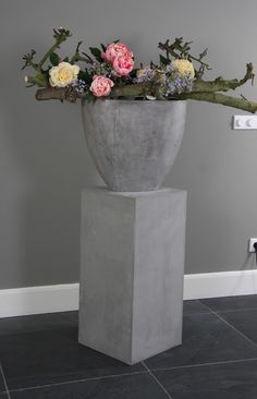 Betonnen vaas op een betonnen zuil met een bloemdecoratie. Verkrijgbaar bij Decoratiestyling