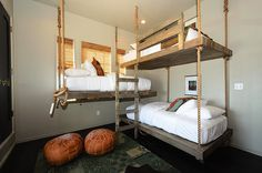 amazing bunk room with rope hung wooden bunkbeds dressed with crisp white bed linens topped with