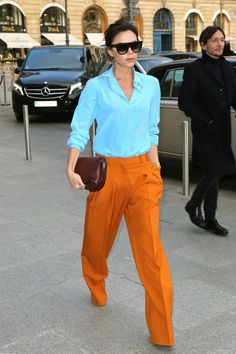 Victoria Beckham Wears Tangerine Trousers, Blue Shirt and Tan Bag From Her Own Collection, Paris, 2017