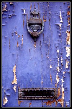 Rust and peeling paint on an old purple door