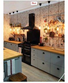 Low hanging light bulbs Hanging utensils Brick effect wall