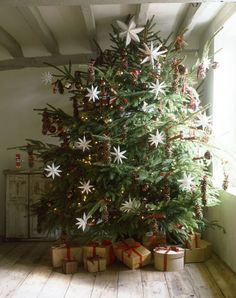 #SwedishChristmas style on this #christmastree with Swedish stars and simply wrapped presents under the tree. #holidaydecor
