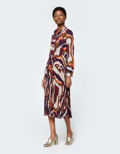Retro-inspired dress from Farrow in Multi. Abstract geometric print. Spread collar. Front button closure. Long sleeves with single button cuff. Gathered elastic waist. Full skirt with accordion pleats. Partially lined.  • Poly chiffon shell, jersey lini