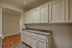Kitchen features TONS of storage space and is open to dining area with gorgeous wood floors and plenty of natural light
