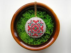 Gamma Folk Cross-Stitched Jewelry    Dainty ladies squeal for delicate cross-stitched pendants.    Available at etsy.com, $25-$42.