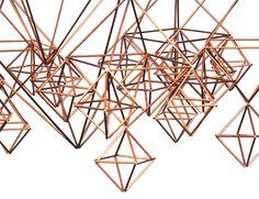 Wiszący obiekt o misternej strukturze z miedzianych rurek, nawiązuje do tradycyjnej formy ludowych pająków.