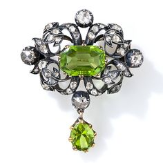 An early-eighteenth century, possibly Georgian, pendant and brooch featuring a glistening pair of lime-green peridots. The central emerald/scissor-cut stone is embellished all around with a shimmering array of rose-cut diamonds set in a graceful foliate design rendered in darkly oxidized silver over rose gold. The oval shape peridot freely swings below. 1 5/8 inch high by 1 3/8 inch wide.
