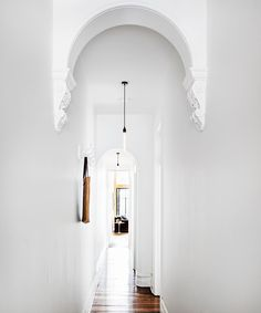 Pendant lights add a modern touch to the traditional hallway. The original floors and the period archways in the front end of the house were maintained.