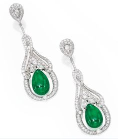 Sotheby's - Pair of 18 Karat White Gold, Emerald and Diamond Earrings.  Set with two emerald drops weighing approximately 27.25 carats, within surrounds set with numerous round and marquise-shaped diamonds weighing approximately 7.40 carats.