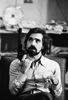 Martin Scorsese holding a gun and grapes during the filming of Taxi Driver (1976), photo by Steve Schapiro