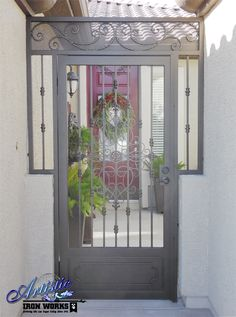 Wrought iron courtyard entry gate with scrolls and knuckles