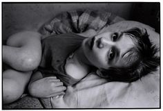 BELARUS. MINSK. 1997. Novinki Asylum. This young boy cannot walk - he spends all of his days silently and alone on his bed.  Paul Fusco/Magnum Photos