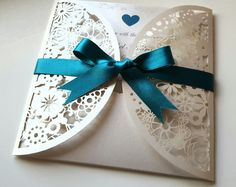 Laser cut pocket wedding invitation in pearlescent ivory tied with a teal satin ribbon bow