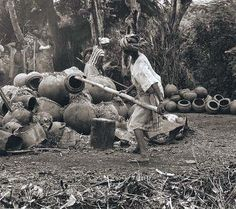 """Final stages in the """"open field firing"""" of terracotta storage vessels. The women in both Arigidi and Erusu (In the Akoko area) employ only """"upside down construction"""". Their pottery skills are unique to this region of Yorubaland. Photo by Ron du Bois, 1988."""