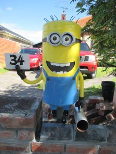 """After what seems like an eternity the minion project is finally in place as the letter box at the front gate.  Built from an old small compressor tank, this minion is a 3D rendition of the cartoon characters from the """"Despicable Me"""" and """"Minions"""" movies. This fellow is not a copy of any one minion, but includes features from a number of the characters. The top teeth and black area inside the mouth are a metal flap hinged inside to fold back for letter insertion."""