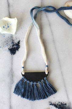 Necklace No. 39. Ceramic half moon pendant with silk tassels, hanging from indigo ombre dyed cotton. Glazed with gunmetal grey. | Halsband. Keramik, halvmåne, siden, indigofärgad bomull.