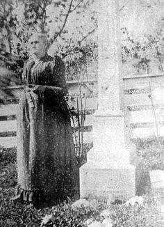 Zerelda James, mother of Frank and Jesse......standing beside Jesse's grave at the family home in Kearney, Mo. He is no longer buried on the farm but at a cemetery in town.