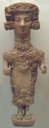 clay figure with elaborately decoated head and dress  	    Goddess from Puig des Molins necropolis, Ibiza. A characteristically Iberian statuette, wearing rodetes suspended beside her ears and a robust floral headdress.