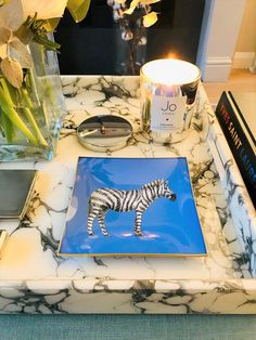 A decorative glass tray featuring a hand-painted zebra illustration, finished with an 18kt gold edge detail. London-based artist, Melissa LaFave uses the traditional decoupage method to merge contemporary design with a classic artistic technique. Looks great on a coffee table, dressing table, desk or wall.