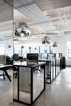 Mirror Balls hand above open plan workspaces at McCann Erickson Offices. Designed by Design Research Studio.