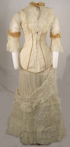 WEDDING DRESS, WHITE ORGANDY, c. 1876.  white organdy and apricot taffeta wedding dress in four pieces: skirt, underskirt, jacket, odd piece; underskirt of crinoline; skirt mass of organdy ruffles and flounces; bodice of white organdy, lined; fringed apricot taffeta trim on three-quarter sleeves and in piping on bodice; undersleeve trimmed in lace; yoke front and back with shirring and ruffles  wedding dress made by Kate White Schuyler at Corning, NY, for her marriage to Andrus Church in…