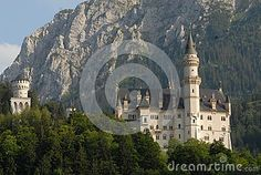 Photo made at the Neuschwanstein castle in Bavaria (Germany). The picture shows the upper part of the castle of King Ludwig II of Bavaria, photographed from the street below. The fiabbesco castle located on a hill seems a fairy tale castle especially for the two towers. Part of the castle is hidden by the trees of the hill on which it stands, behind you see the rock of the mountain that closes the valley.
