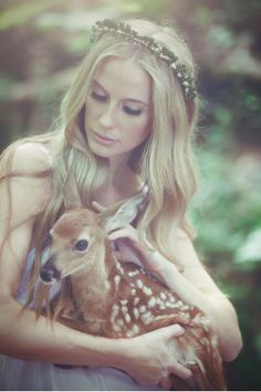 """Fauna picked up the young doe. """"There,there."""" She told the frightened and injured animal."""