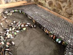 Glass bottle sub-floor,Because the glass bottles hold a layer of air between the dirt and the concrete floor, it acts as a blanket under the floor, keeping the house temperature more stable Wine Bottle Wall, Bottle House, Beer Bottle, Bottle Garden, Maison Earthship, Earthship Home, Natural Building, Green Building, Building A House