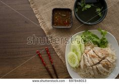 """Chicken Rice with sauce and soup """"Khao Man Kai"""" on wooden desk (Hainan Chicken)"""