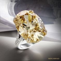 An exceptionally rare, oval, deep yellow diamond of 32.15 carat in the Deep Sunburst ring by Mouawad