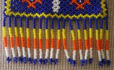 This necklace is handmade with glass seed beads also known as Chaquira. It has the Ojo de Dios (Gods eye) symbol. The Ojo de Dios is a symbol meaning the power of seeing and understanding that which is unknown and unknowable, The Mystery. The symbol also represents the Protection for Kids and the four points also represent the elements of earth, fire, air and water. The colors on this necklace are Blue, Yellow, Orange and white. Measurements: Length:17.1/2 Opening:12.3/4  Symbol Siz...
