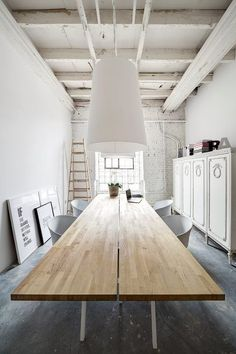 Long wooden table in a white dining room