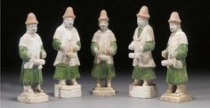 Five Ming pottery models of drummers each standing wearing tall red hats and tunics, the under garments glazed green, set upon raised square bases. Christie's.