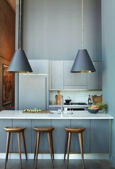 12 Kitchen Counters: Another dark kitchen scheme designed by Athena Calderone. This time it's her penthouse in Brooklyn's Dumbo neighborhood, which overlooks the East River. The brass interiors of the oversized Thomas O'Brien conical pendant lights play off the smooth wood stools from Organic Modernism.