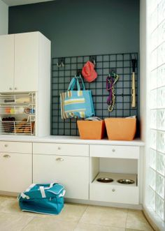 Large cabinets hide supplies and gear, while pullout metal bins contain sports accessories in full view. Above the counter, a wall-hung metal grid with hooks provides a place for dog leashes, coats, etc. The same tools keeping the garage tidy work wonders combined in a command center. Paint the wall to infuse color & avoid a sterile, utilitarian look.