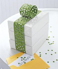 Bright construction paper becomes an offbeat ribbon with the help of a hole punch and some double-sided tape. | Creative Gift Wrapping Ideas | Real Simple Mobile