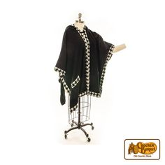 Enjoy cool winter days wrapped up in our elegant women's wrap. This black wrap features a houndstooth pattern lining the trim and pockets, with a black hook closure at the neck.    Answer fun questions and you could win in the Cracker Barrel Old Country Store Pick it to Win it Sweepstakes. Start 'picking' your answers at crackerbarrel.com/win (ends Jan 2, 2013).