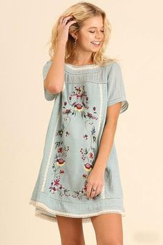Classic A-line dress in Light Blue featuring floral embroidery throughout. Short-sleeved and fully lined. Pullover style with single button at nape of neck. Add a pair of our B123 Seamless Capri Leggi
