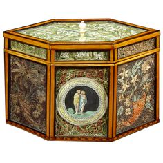 A George III Quillwork Tea Caddy Of Hexagonal Form, England, CIRCA 1790. Decorated with floral panels; the front central panel with applied handtinted medallion of two classical figures.