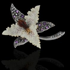 """Realistically rendered Orchid brooch in silver set with old-cut diamonds and cabochon amethysts with 18ct yellow gold petals with matte cream enamel around a central diamond-set silver stigma enamelled in red and yellow tones to the underside. French, Fin de siècle, circa 1889."""