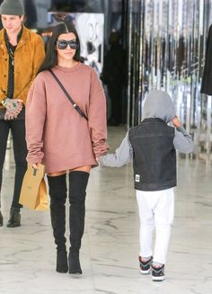 Kourtney Kardashian wears black over-the-knee boots with an oversized sweatshirt dress and statement shades.