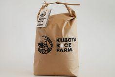 「窪田梨果園」様の新しい米袋とロゴマークを担当させていただきました。 今回依頼をいただいたのは江南区(旧亀田町)で梨や米を栽培する窪田梨果園様。 梨果園という名前の通り、日本梨やル・レクチェの生産がメインなのですが、今後は米の販売にも力を入れていきたいという事で新しく「KUBOTA RICE FARM」というロゴマークと米袋を作ることになりました。 ちなみに、窪田梨果園様の梨は新潟直送計画で購入可能です。 《窪田梨果園紹介ページ》 また、二人の若い担い手の顔写真やHPのQRコード、SNSのURLなどの情報も掲載したいと思い、名刺サイズのタグも制作させていただきました。 「新潟亀田で情熱、米(こめ)てます」というコピーは窪田梨果園様で考えられたもです。 コンセプト 二人の若い担い手が男らしく情熱的に農業に取り組まれている姿勢が印象的だったので、頂いたラフ案に男らしさや情熱的な雰囲気をプラスしました。 タイプフェイス 男らしく力強い欧文のゴシックフォントをベースに、角を全て丁寧に丸くとって、農業に対する力強くも丁寧な姿勢を表現しました。…