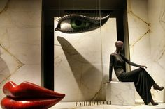 WindowsWear | Emilio Pucci, New York The oversized features of the face grab your attention first using the pyramid effect. My eyes went directly to the red lips then the hanging eye then to the mannequin. Because Emilio Pucci is a more high-end designer they can afford to have only one mannequin and such elaborate display props. The display definitely says high-end to me