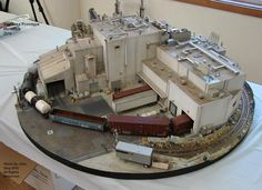 """""""The train runs in a loop - you just had to see it to appreciate how amazing it looked in action. Info about (…): the show stopper might have been the above by Greg Malinowski. It's an insanely good little crazy detailed/kitbashed/weathered """"Bay Freight Division"""" - a small 36"""" diameter layout built on a perfectly round 1"""" thick piece of plywood! Those inside hidden curves and ones leading into the paved diamond crossing are about a 12"""" radius!"""""""