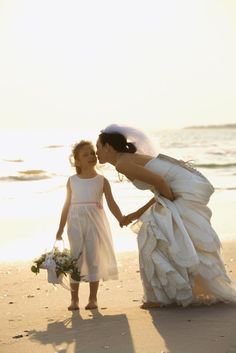 Bride and flower girl. - Caucasian mid-adult bride kneeling to give flower girl a kiss on the cheek while holding hands barefoot on beach. San Diego Wedding Venues, Wedding Abroad, Bride Flowers, Wedding Honeymoons, Beach Girls, Beach Resorts, Photo Poses, Royalty Free Photos, Wedding Events