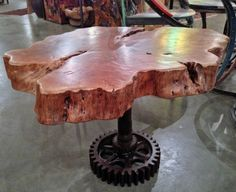 A custom side table made from a cross cut section of reclaimed lychee fruit wood tree and a salvaged steel base.  Custom by Impact Imports