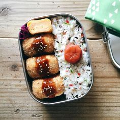 Korokke (croquette) bento box, with sides of tamagoyaki, pickled red cabbage, and furikake rice topped with umeboshi.