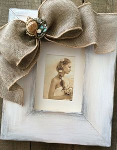 Unique Beach themed Photo Frame, will complement your photos from a wedding at sea, a tropical honeymoon, or a family day of sand & surf! The hand distressed wood is finished in rustic white tones with lots of texture. Your preferred bow choice is accented by a clustered jewel arranged with shells, baubles & rhinestones. Select optional personalized plaque for a thoughtful gift giving touch (example in last photo). Specify name/s, date, or special word. Includes finished easel ba...
